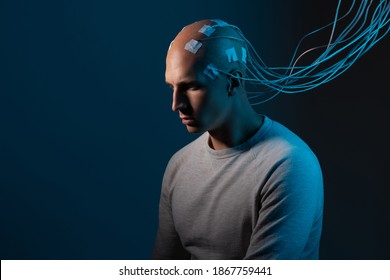 man with electrodes in his head is a futuristic concept of virtual reality and mind control. Neuro interface, contact of biological and mechanical