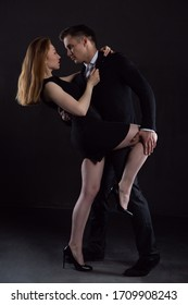 A man in an elegant black suit holds a sexy girl who is embracing him behind his back