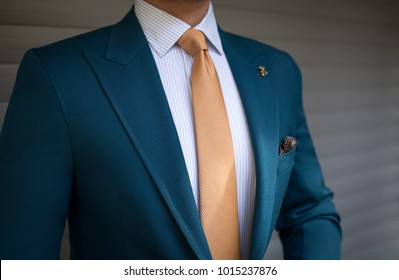 Man in elegant custom tailored expensive suit posing in front of background