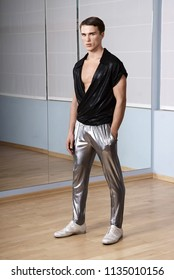 Man in elegant sport suit posing in fitness gym. Young man in silver sport leggings