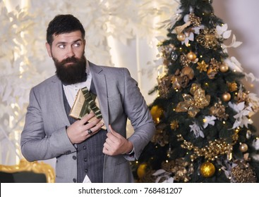 A man in an elegant suit hides a gift hidden under his jacket. Handsome new year man with long beard and moustache. The Christmas mood with gifts, christmas tree, holidays, celebration, surprise.
