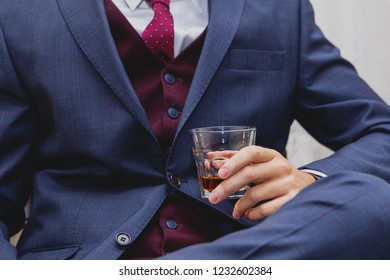 man in elegant suit holding glass with alcohol drink