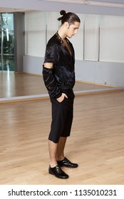 Man in elegant suite posing in fitness gym. High fashion young sexy man in black shorts and a black jacket.