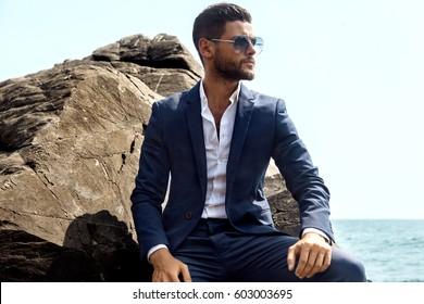 Man in elegant suite posing in rock background