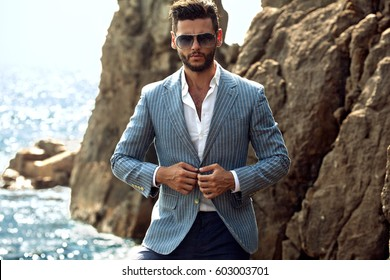 Man in elegant suite posing in rock background