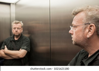 Man in the elevator looking at himself skeptically in the mirror