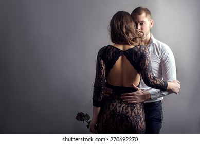 man embraces woman in evening dress