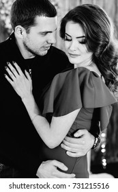 Man embracing his beautiful wife while she looks down, black and white portrait
