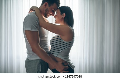 Man embracing his pregnant woman looking into each other's eyes