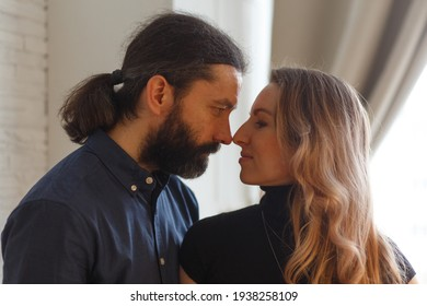 Man embracing pregnant partner in kitchen. Adult family pregnancy concept. Future parents in home outfit embrace standing in the kitchen, looking at each other, kissing. Healthy Lifestyle.