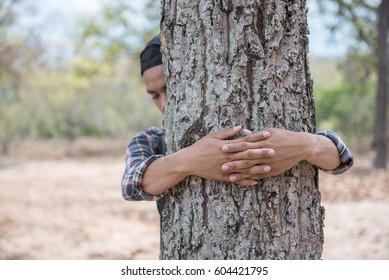 A man embracing a tree in the forest