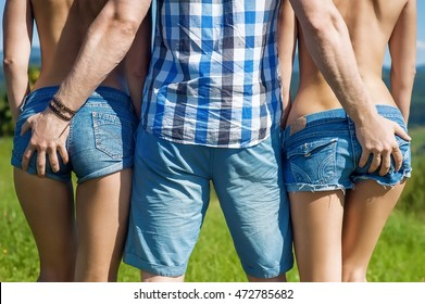 man embracing two women dressed in denim shorts