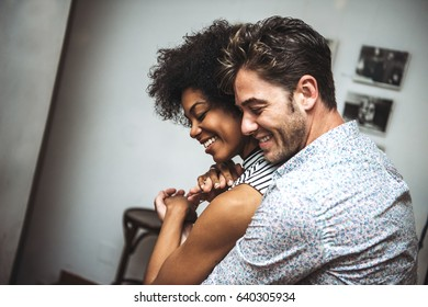 Man embracing woman from back and dancing with eyes closed in bar.