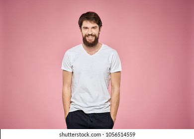 man with emotions on his face with a beard on a pink background, logo, copy space