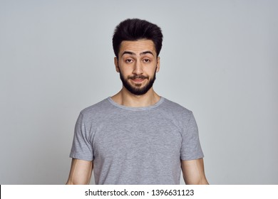 man with emotions on his face in a t-shirt on a gray background
