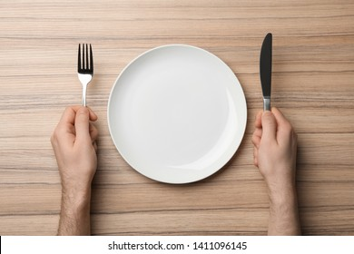 Man with empty plate and cutlery at wooden table, top view