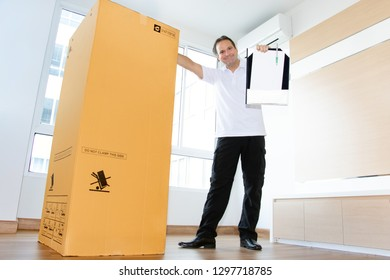 A man in an empty room shows a blank paper document for shipping large package. The postman delivers the parcel to the new apartment.