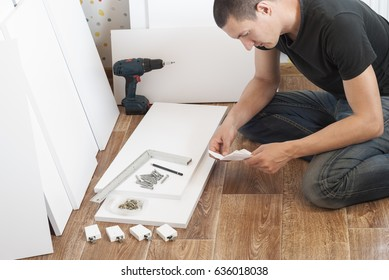 man is engaged in assembling furniture in the house