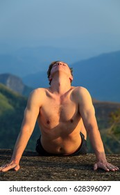 Man is engaged in physical exercises among the mountains. The concept of a healthy lifestyle.