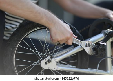 A man engaged in repairing a bicycle with a spanner in his hand