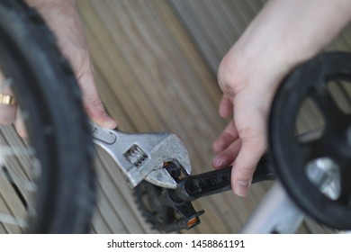 A man is engaged in repairing a bicycle wheel with a tool in his hands.