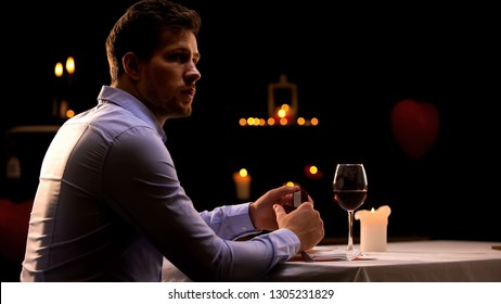 Man with engagement ring sitting alone in restaurant, hoping his girlfriend come
