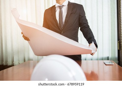 Man engineer with plan paper on desk