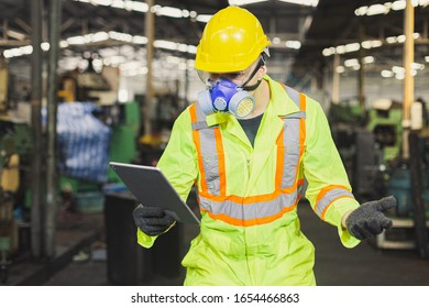Man engineer wearing safety uniform with gloves and gas mask and tablet.