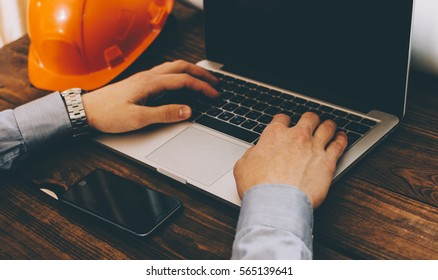 Man engineer working at the laptop on wood table with hardhat
