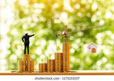 Man engineers in hard hat helmet is working on stack gold coin with grow value and tower crane with build house in the public park, saving money and loan for construction real estate and home concept.