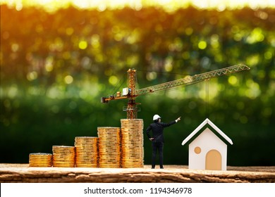 Man engineers in hard hat helmet is working and stack gold coin with grow value and tower crane with build house in the public park, saving money and loan for construction real estate and home concept