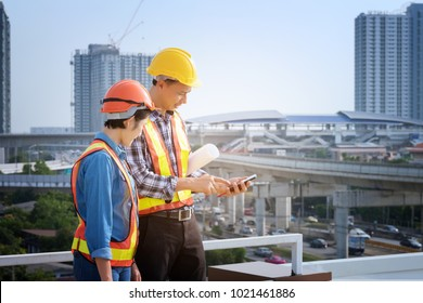Man Engineers stand on tall buildings and talk about cell phones in the field of construction. Engineers are meeting, working and looking at drawing in mobile, building background