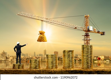 Man engineers is working on stack gold coin with grow value and tower crane and hoist brake with money bag on photo blur cityscape background, Loan and budget  for construction real estate concept.