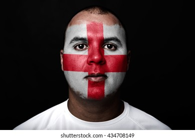 Man with England flag painted on her face on black background