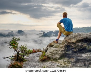 Man enjoy fantastic dreamy sunrise on top of rocky mountain with view into misty valley. Mountain view. Foggy mountain peak. Dreamy forrest.  Sunrise clouds.