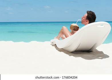 Man enjoy lying on lounger sunbed and drinking coconut cocktail on beach with white sand and blue indian ocean. Summertime at paradise place at Maldives