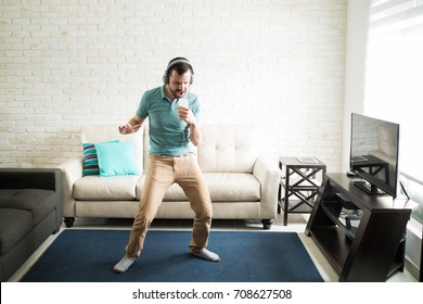 Man enjoying an afternoon alone at home by singing karaoke with his phone in the living room