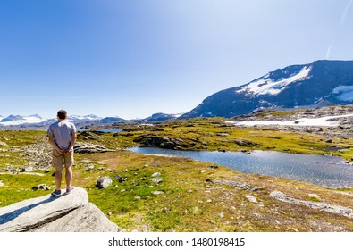 Man enjoying the beautiful landscape along National scenic route Sognefjellet between Skjolden and Lorn in Sogn og Fjordane in Western Norway.