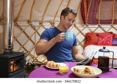 Man Enjoying Breakfast Whilst Camping In Traditional Yurt