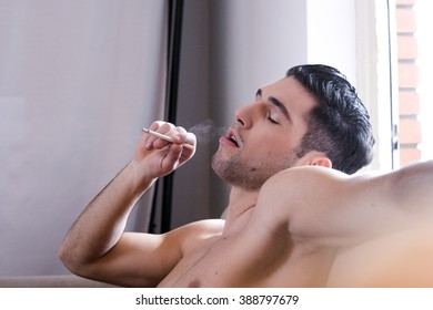Man enjoying a cigarette shirtless