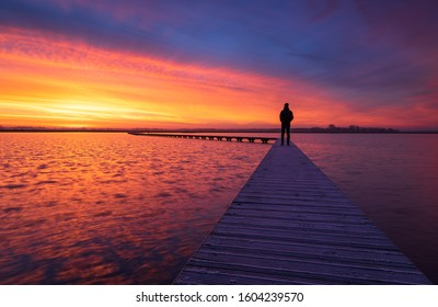 A man enjoying the colorful  dawn on a jetty in a lake. Groningen, Holland.