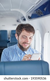 Man enjoying his journey by airplane and using mobile phone for calls and messages