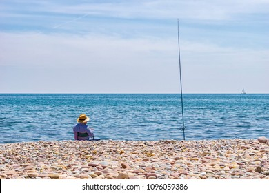 Man enjoying his retirement fishing by the seashore, on a pebble beach, during a beautiful sunny day, while watching the yachts sailing in the distance.