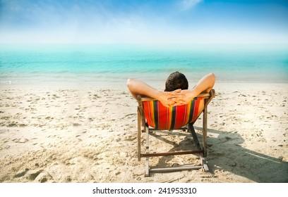 Man enjoying lazy afternoon at the beach.