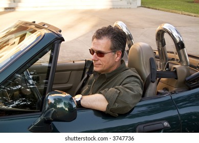 A man enjoying a leisurely drive, with the top of his sports car down.