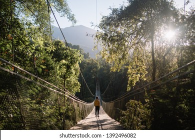 A man is enjoying morning scenery on Situgunung Suspension Bridge, South-East Asia's longest Suspension Bridge located in the middle of the forest of Indonesia.