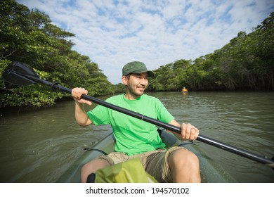 Man enjoying river kayaking in lush mangrove forest, Ishigaki Island of the Yaeyama Islands, Okinawa, Japan