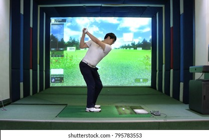A  man enjoying screen golf with 7-iron backswing top motion, South Korea; Korean on the screen means information on swing and environmental condition