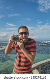 Man enjoying summer with his retro camera on the sea / ocean.