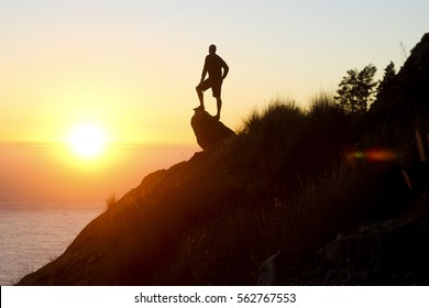 A man enjoying the sunset at the peak of a hill